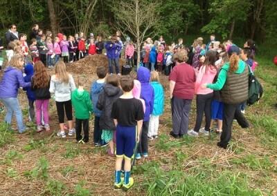 Kids gathered around oak tree donated by Mahonia Nursery
