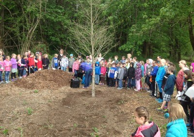Kids gathered around oak tree donated by Mahonia Nursery